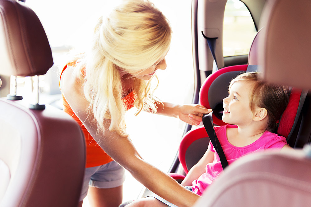 mom putting baby in car seat